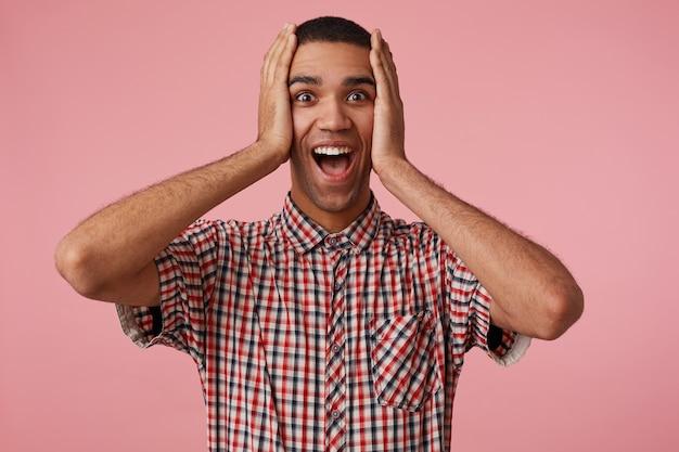 Wow! il giovane ragazzo dalla pelle scura attraente calzino ha vinto un'auto, guarda la telecamera con la bocca e gli occhi spalancati, si leva in piedi su sfondo rosa e si tiene la testa, indossa una camicia a scacchi. Foto Gratuite