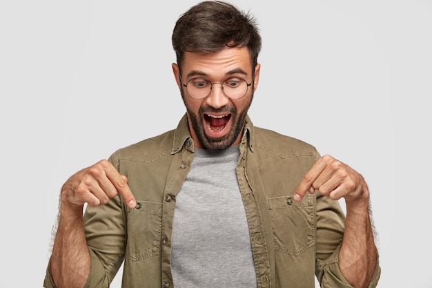 Wow, that`s amazing! amazed shocked young male looks with surprisement down, points with both index fingers, dressed casually, opens mouth widely in astonishment, isolated over white wall Free Photo