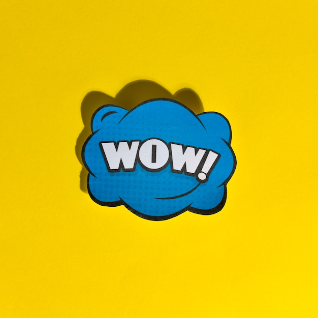 Wow word pop art retro vector illustration on yellow background Free Photo
