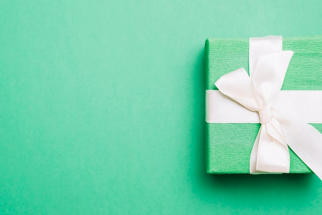 Wrapped birthday present with white ribbon bow on green background Free Photo