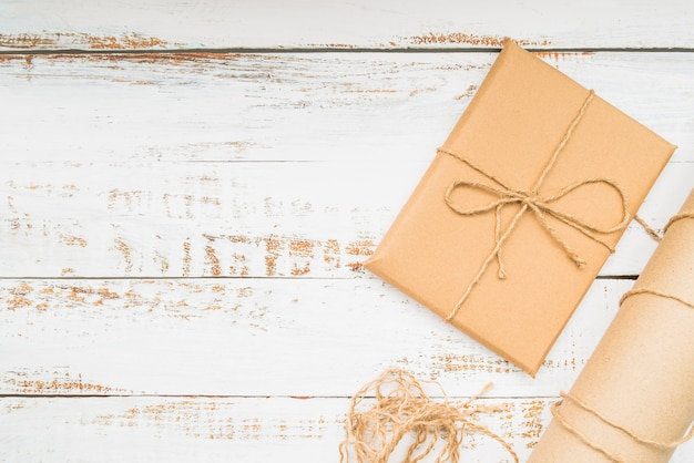 Wrapped brown gift paper gift box on wooden background Free Photo