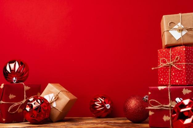 赤い背景の正面に対してラップされたクリスマスギフトボックス Premium写真