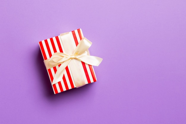 Wrapped christmas handmade present in paper with yellow ribbon on purple Premium Photo
