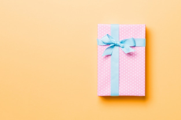 Wrapped christmas or other holiday handmade present in paper  blue ribbon on orange . Premium Photo