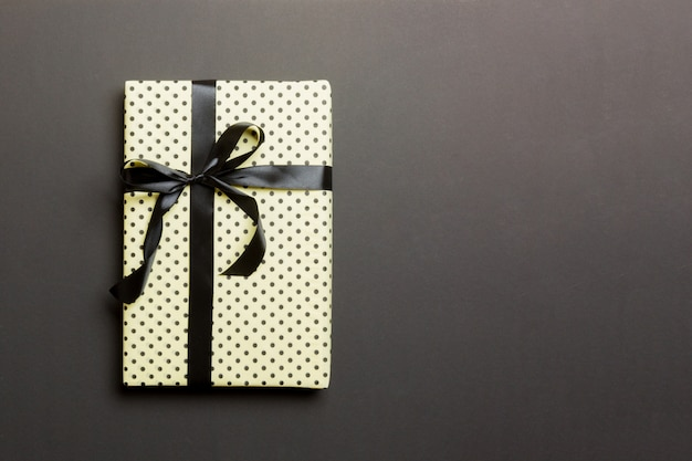Wrapped christmas or other holiday handmade present in paper with black ribbon on black background Premium Photo