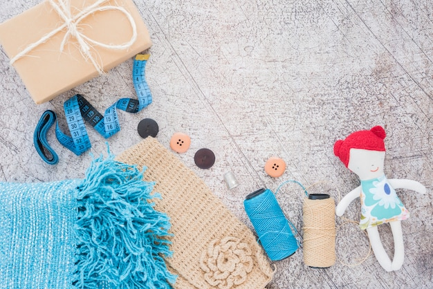 Wrapped gift box; measuring tape; buttons; spool and doll on textured backdrop Free Photo