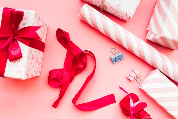 Wrapped gift box with red ribbon; gift paper and paperclip on pink background Free Photo