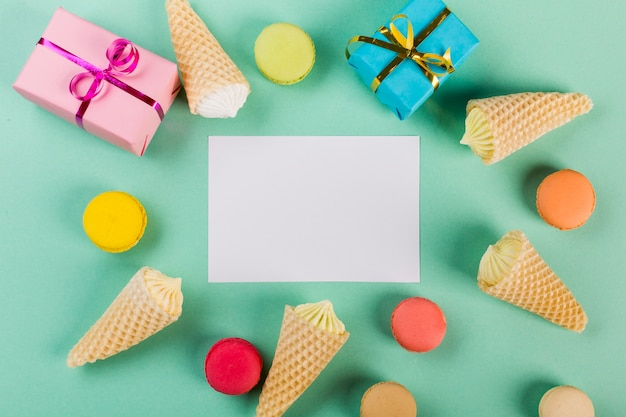 Wrapped gift boxes; macaroons and waffle with aalaw around the white paper on mint green backdrop Free Photo