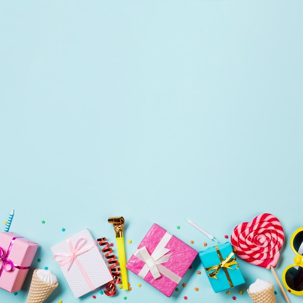 Wrapped gift boxes; waffle one; streamer; sunglasses and heart shape lollipop on blue backdrop Free Photo