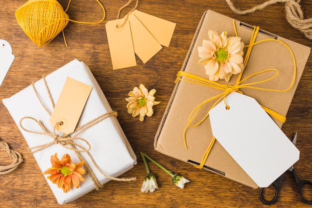 Wrapped gift tied with tag string and beautiful flower on wooden surface Free Photo
