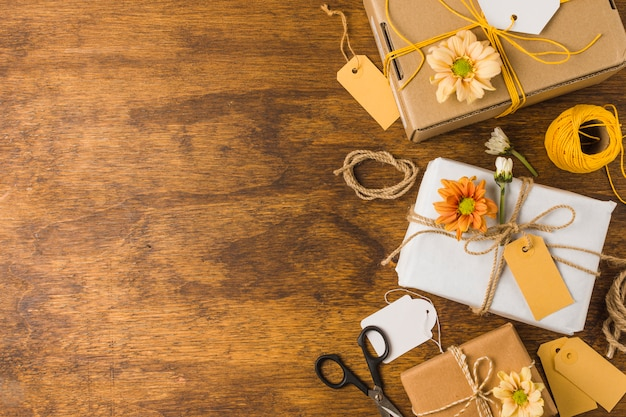 Wrapped gift with empty tag and beautiful flower over wooden table Free Photo