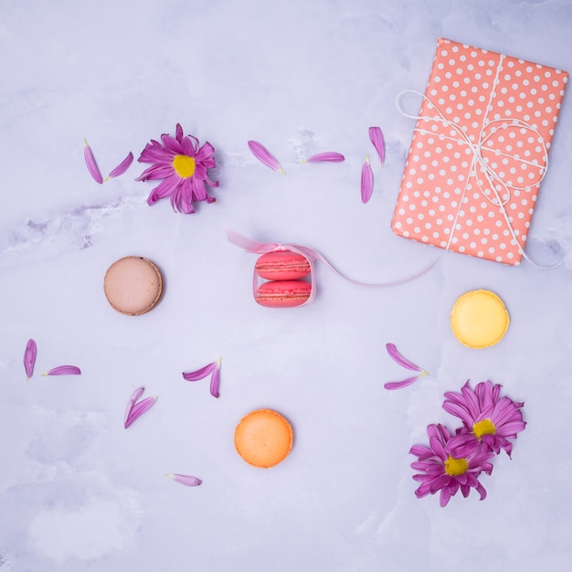 Wrapped gift with purple flowers and macarons Free Photo