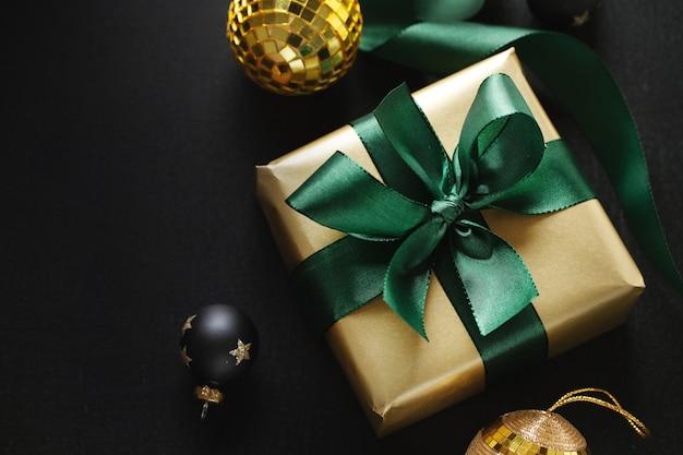 Wrapped golden gift with green bow and baubles on black. flat lay. Premium Photo