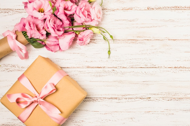 Wrapped pink eustoma flower and gift box on white old table Free Photo