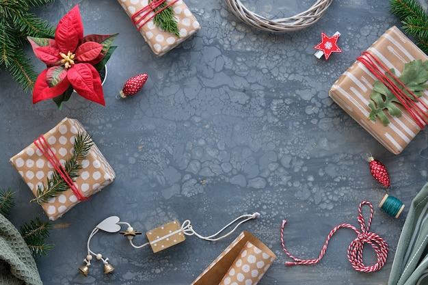 Упаковка рождественских подарков, подарков в крафт-бумагу, оберточную бумагу с абстрактными точками и полосами. рождественский фон с подарочными коробками, еловыми ветками, текстилем на темно-сером столе с копией пространства. Premium Фотографии