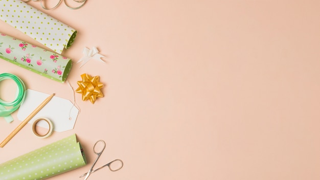 Wrapping paper roll; sellotape; pencil; ribbon bows and scissor arranged in peach surface with space for text Free Photo