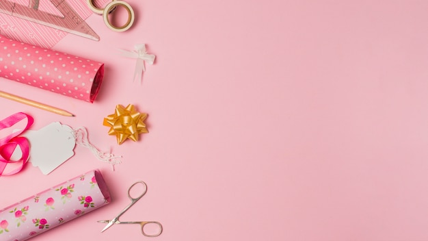 Wrapping paper; scissor; tag and stationery materials on pink wallpaper with space for text Free Photo