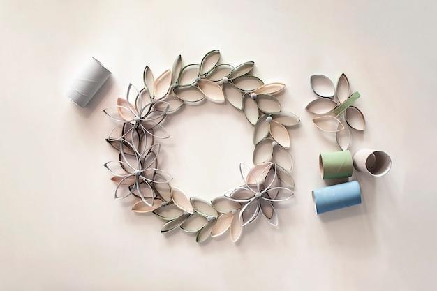 イースターのお祝いのためのトイレットペーパーチューブからの花輪、子供のためのゼロウェイストクラフト、ニュートラルパステル Premium写真