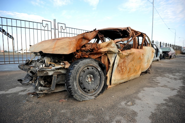 Wrecked and burning car on the road Premium Photo