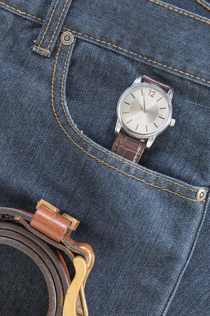 Wrist watch and leather belt on jeans Premium Photo