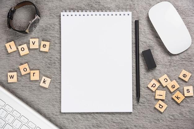 Wrist watch; love work desk blocks with office supplies on gray backdrop Free Photo