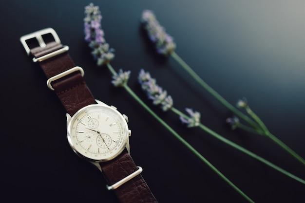 黒の背景にラベンダーの小枝が付いた革ストラップの腕時計。 Premium写真