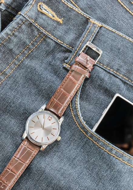 Wrist watch and smartphone on jeans Premium Photo