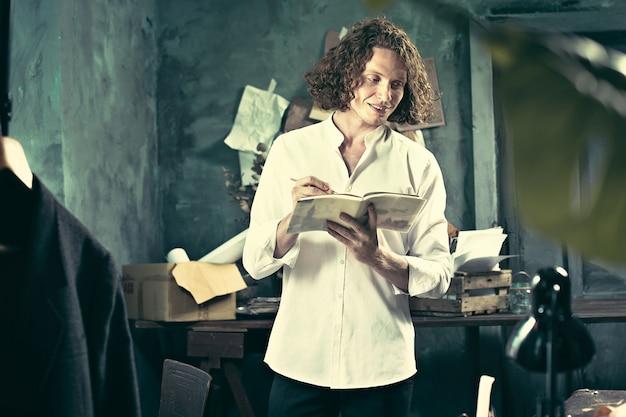 Писатель за работой. красивый молодой писатель стоит возле стола и что-то придумывает Бесплатные Фотографии