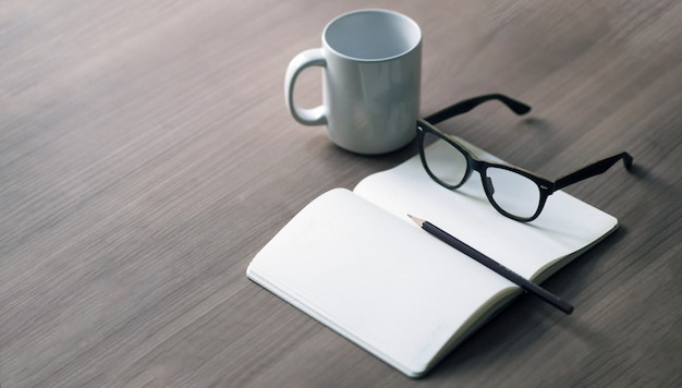 Writer's career on the desk with a white coffee mug, pencil and glasses book Premium Photo