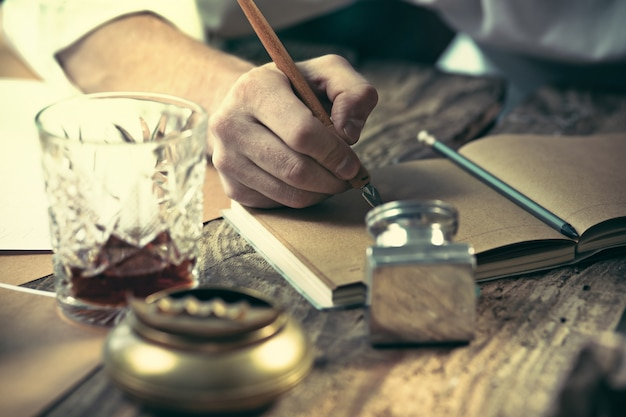 Writer at work. the hands of young writer sitting at the table and writing something in his sketchpad Free Photo