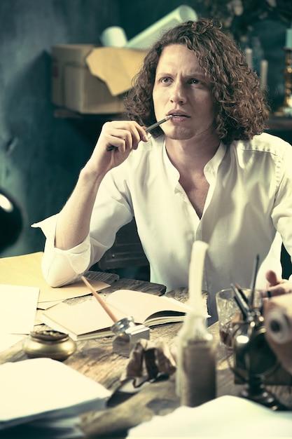Scrittore al lavoro. bel giovane scrittore seduto al tavolo e scrivere qualcosa nel suo taccuino a casa Foto Gratuite