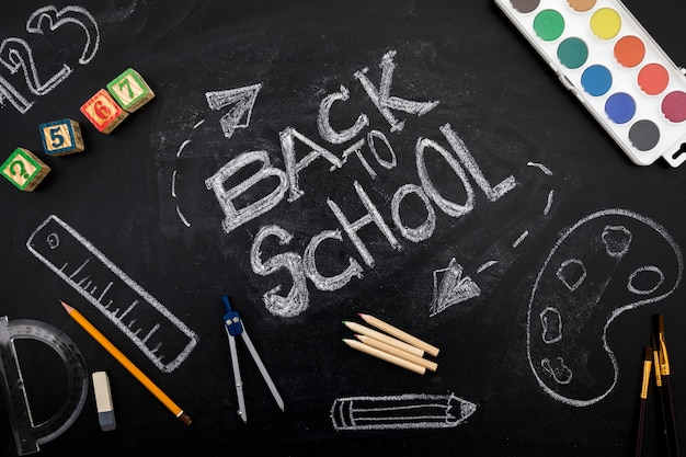 Writing on blackboard in chalk with stationery Free Photo