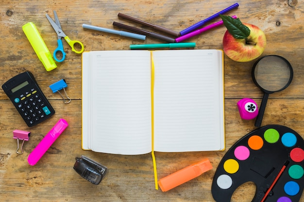 Writing implements and apple laid in circle with notebook in middle Free Photo
