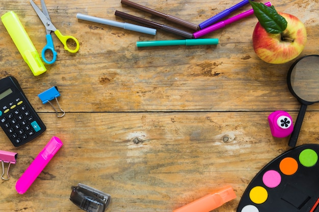 Writing implements and apple laid in circle Free Photo