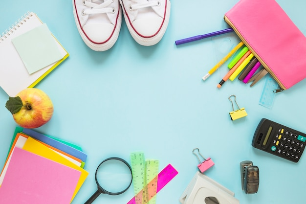 Writing implements and sneakers laid in circle Free Photo