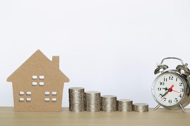 コインのお金とwtite背景にモデルハウスのスタック Premium写真