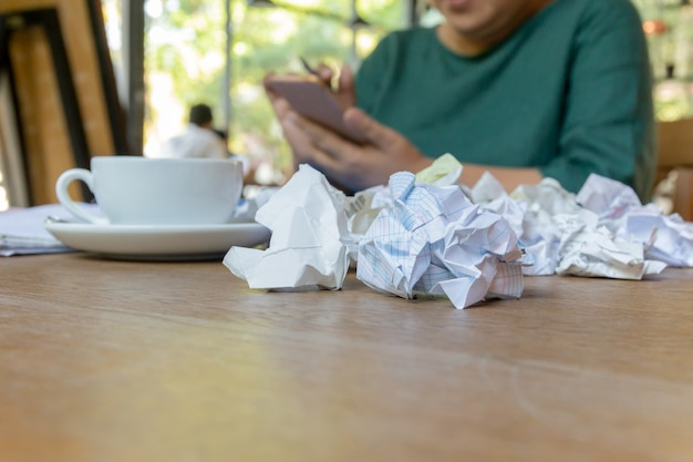 Wwoman hand using cell phone working after hours with crumpled paper on table. Premium Photo