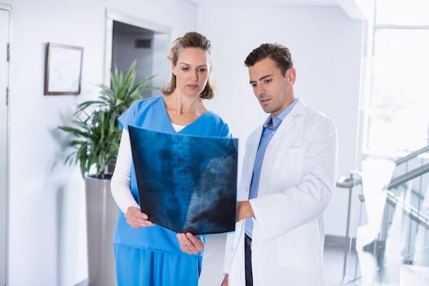 廊下で患者のx線を見ている2人の医師 Premium写真