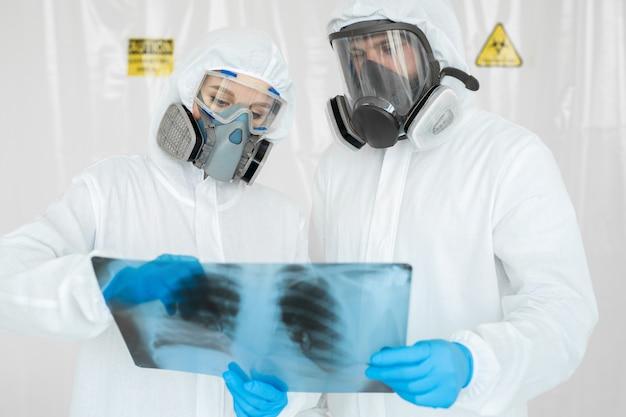 呼吸器の疫学者は、x線写真covid-19で患者の肺炎を調べます。コロナウイルスの概念 Premium写真