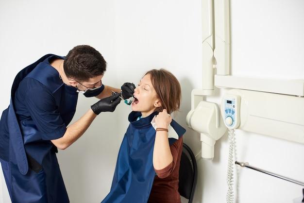 歯科医は歯科医院でx線撮影を行う患者を治療しています Premium写真