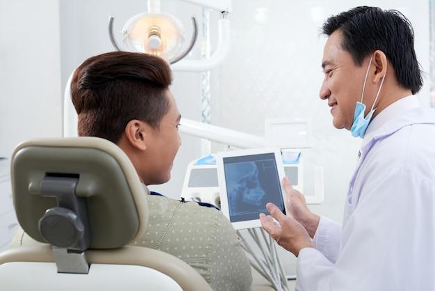 タブレットで患者に顎のx線画像を示すアジアの男性歯科医 無料写真