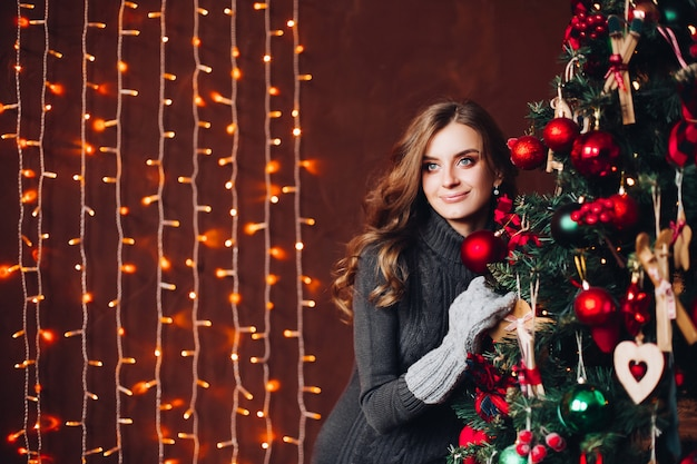 装飾されたxマスツリーに対して灰色のドレスに立って美しい女性。 Premium写真