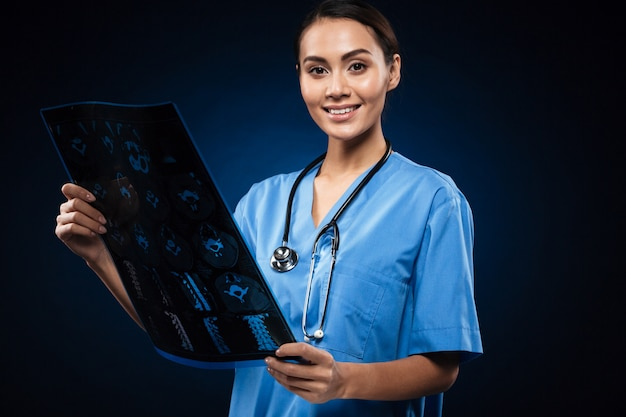 X線画像を見て制服を着た笑顔ブルネット医師 無料写真