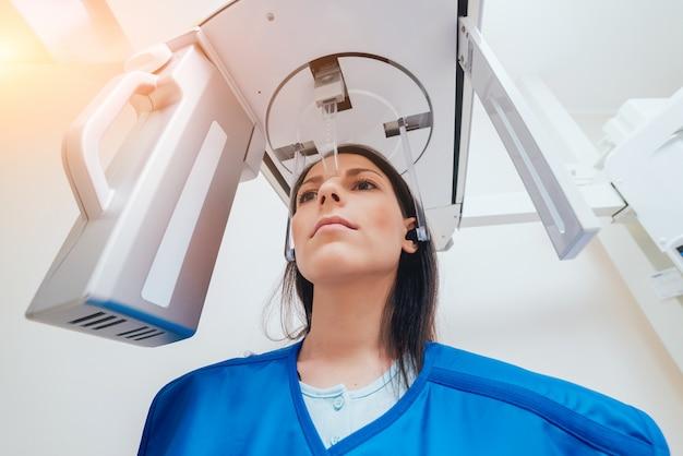 X線装置に立っている若い女性患者。 Premium写真