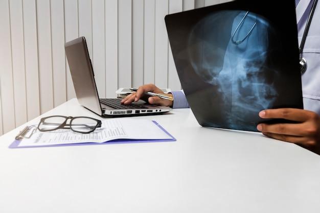 医師は患者のx線フィルムを診断して分析します Premium写真
