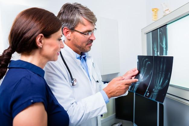患者の手のx線写真を持つ医師 Premium写真