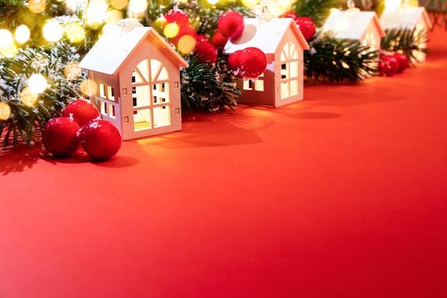 Рождественский фон. светящиеся рождественские огни белых домиков, еловые ветки, красные ягоды, огни боке, стоящие по диагонали на красном. уютная праздничная рождественская атмосфера. рождество дома концепции. скопируйте пространство. Premium Фотографии