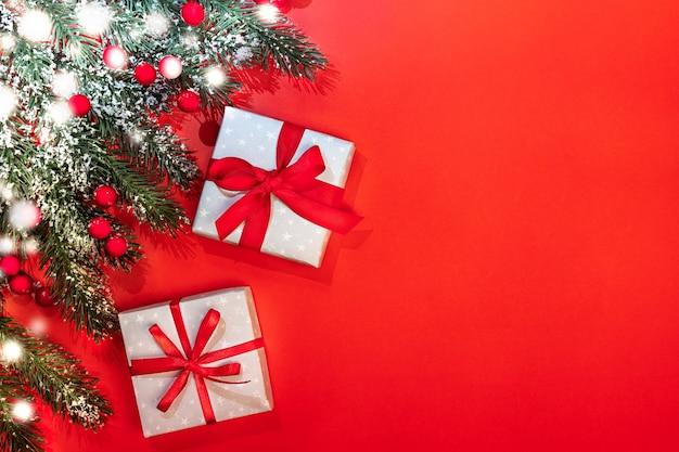 Рождественский праздничный фон с еловыми ветками, покрытыми снегом, красными ягодами, двумя подарочными коробками diy, перевязанными лентами и бантами на красном. Premium Фотографии