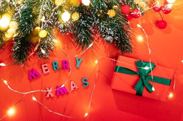 Рождественские праздничные открытки. еловые ветки и светящиеся рождественские огни с красивыми тенями, снегом, красными ягодами, цветными буквами merry xmas, подарочной коробкой diy, золотыми огнями боке на красном фоне. вид сверху. Premium Фотографии
