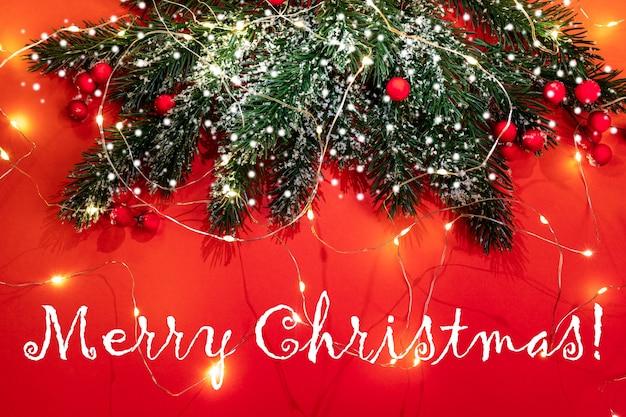 Рождественская праздничная открытка с еловыми ветками, снегом, красными ягодами, светящимися рождественскими огнями на красном фоне с надписью с рождеством. атмосфера праздника. вид сверху. Premium Фотографии